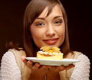 Young woman eats a sweet cake Royalty Free Stock Photos