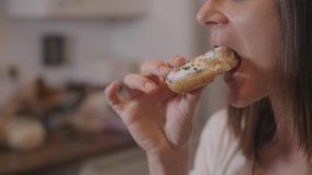 Young woman eats sweet sugar doughnuts. Home shooting stock photo