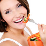 Young woman eats vegetable Royalty Free Stock Photo