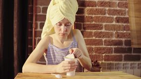A young woman eats yogurt from a large white jar near a brick wall. stock video footage