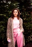 Young woman in eco fur and pink clothes walking on the Christmas decorated street royalty free stock images