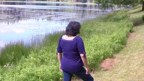 Young woman at the edge of a lake stock footage