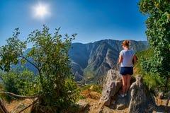 Young Woman at the edge of Mountain Gorge. Near Tatev Monastery in Armenia Royalty Free Stock Photos