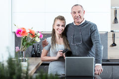 Young woman and elderly man portrait. Beautiful young women and elderly men with glasses on his neck standing in kitchen with dslr camera in hands and laptop on stock photography