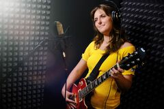 Young woman with electric guitar and headphones at the recording Studio. Professional recording of musical instruments for a new