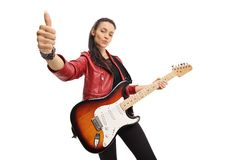 Young woman with an electric guitar showing thumbs up. Isolated on white background royalty free stock image
