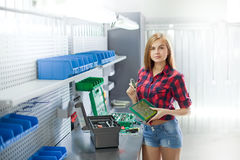 A young woman with electronic plate in a garage. Female mechanic at work. auto service station. Young brunette woman working in the garage royalty free stock photography