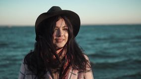 Portrait of cute girl closeup on sea background. young woman in autumn coat and hat posing and smiling at the camera stock video