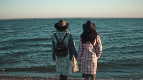 Girlfriend standing on the sea shore and enjoy the view. two young woman in autumn coat at sunset. the view from the stock video