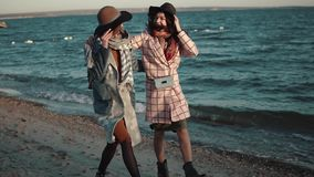 Two girlfriends happily run around and frolic in the open air. young woman in autumn coat and hat on the beach at sunset. Young woman in elegant coat walks on stock video footage