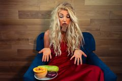 Young woman in elegant red dress sits on armchair with chocolate in teeth stock photo