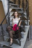 Young woman in elegant summer evening clothes sitting in staircase waiting Royalty Free Stock Images