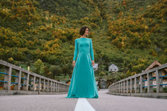 Young woman in an elegant turquoise dress on the bridge Royalty Free Stock Photography