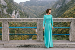 Young woman in an elegant turquoise dress on the bridge Royalty Free Stock Photos