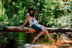 Young woman elegantly sits on a log against the wood and the river. Royalty Free Stock Images