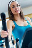 Young woman with elliptic machine in the gym. Portrait of young woman with elliptic machine in the gym Stock Image
