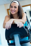 Young woman with elliptic machine in the gym. Portrait of young woman with elliptic machine in the gym Royalty Free Stock Photos