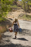 A Young Woman Embarks On A Trip. A young lady walks away from the camera, with two old suitcases in hand, adding to a somewhat vintage feel royalty free stock image