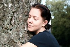 Young woman embrace big tree. Young woman embrace a big tree in the nature with closed eyes Stock Photography