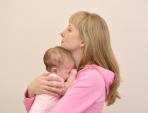 The young woman embraces the crying baby Stock Photo