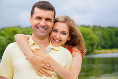 Young woman embraces man from back stock images