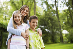 Young Woman Embracing Children In Park Royalty Free Stock Photography