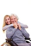 Young woman embracing disabled. Elderly woman in wheelchair Stock Photography