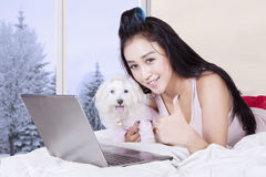 Young woman embracing dog with laptop. Image of pretty girl showing thumb up and lying on the bed while embracing a maltese dog with laptop in the bedroom Stock Photo