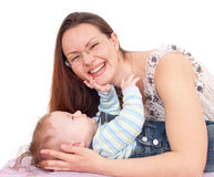 Young woman is embracing her baby. Young mother with her baby on white background Stock Photos
