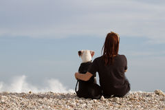 Young woman embracing her dog looking at sea Stock Photography