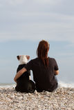 Young woman embracing her dog looking at sea Royalty Free Stock Photo