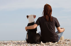 Young woman embracing her dog looking at sea Stock Image