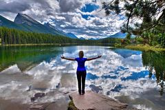 Young woman embracing the lake with reflections of clouds and mountains. Stock Images