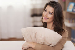 Young woman embracing pillow Stock Images