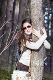 Young woman embracing a pine stem in the  forest Stock Image