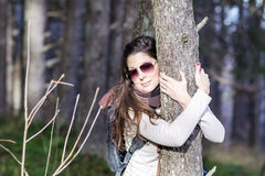 Young woman embracing a pine stem in the  forest Royalty Free Stock Photography