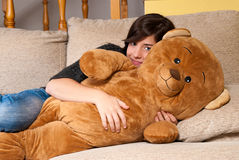 Young woman embracing teddy bear lying on on sofa Stock Photo