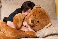 Young woman embracing teddy bear lying sofa close Stock Images