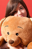 Young woman embracing teddy bear sitting close-up stock photo