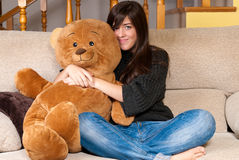 Young woman embracing teddy bear sitting on sofa Stock Photo