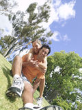 Young woman embracing young man in running clothes in park, smiling, portrait (tilt). Young women embracing young men in running clothes in park, smiling Royalty Free Stock Images