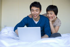 Young woman embracing young man using laptop on bed, smiling Stock Photography