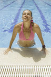 Young woman emerging from the pool Royalty Free Stock Images