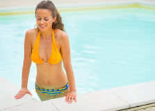 Young woman emerging from swimming pool Stock Image