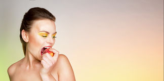 A young woman emotionally bites off a peach. Royalty Free Stock Photography