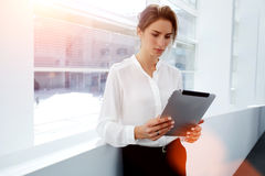 Young woman employee watching video or reading newspaper on digital tablet while standing in modern office interior, Royalty Free Stock Images