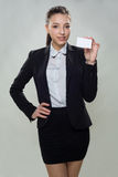 Young woman with empty business card. On gray background Stock Photo