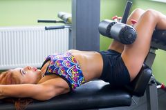 Athletic woman trains press in sport gym Stock Images