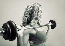 A young woman is engaged in weightlifting stock photography
