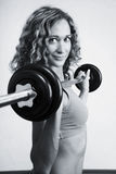 A young woman is engaged in weightlifting Stock Photos